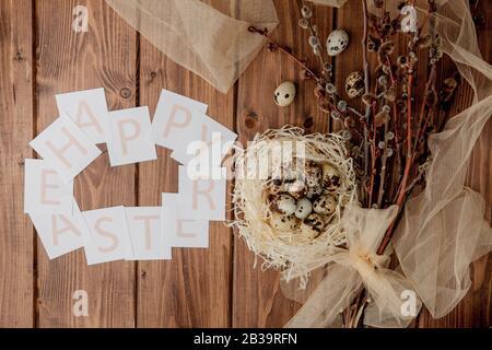 Flache Laienzusammensetzung aus Wachteleiern und Karte mit Text Happy Easter auf Holztisch. Draufsicht. - Stockfoto