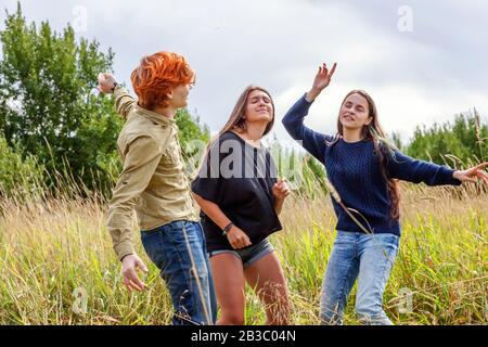 Sommerferien Urlaub glückliche Menschen Konzept. Gruppe von drei Freunden Junge und zwei Mädchen tanzen und Spaß zusammen im Freien haben. Picknick mit Freunden auf dem Weg in die Natur - Stockfoto