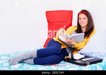 Schöne junge Frau, die bequem auf einem Bett in ihrem Schlafzimmer sitzt und ein Notizbuch hält, lächelt und die Kamera betrachtet. Lächelndes Mädchen, das sich im Bett entspannen kann.