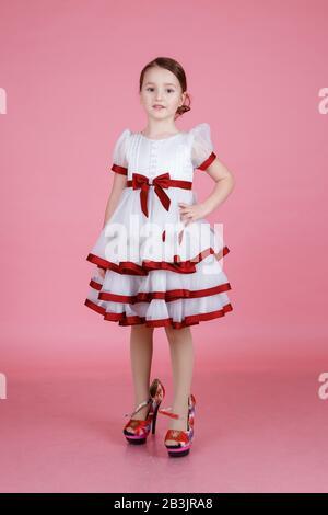 Porträt des niedlichen kleinen Mädchens, das in weißem Kleid in den Schuhen der Mutter auf dem rosafarbenen Hintergrund im Studio steht. Konzept für Liebe und Pflege - Stockfoto