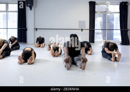 Mixed Race moderne Tänzerinnen, die sich in einem Studio ausdehnen Stockfoto