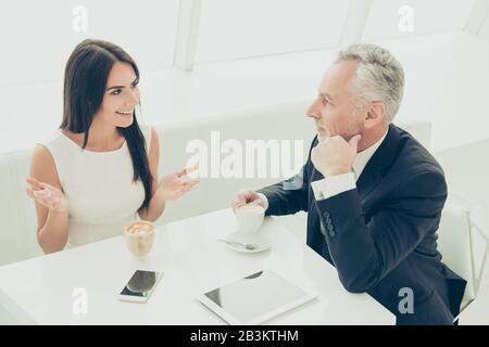 Zwei Geschäftsleute trinken während des Mittags Kaffee und diskutieren Geschäftsessen - Stockfoto