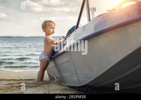 Süßer liebenswertes kaukasisches blondes kleines Kleinkind in weißer Hose am Strand in der Nähe von Fischerboot Blick und träumend von Seemannschaft in - Stockfoto