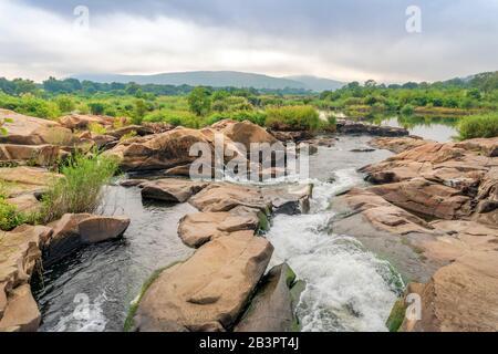 Stream mit Felsen in der Nähe der Krokodilbrücke im Kruger National Park, Südafrika Stockfoto