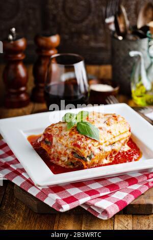 Klassisches Lasagne Stück auf einem Teller mit Basilikumblatt oben - Stockfoto