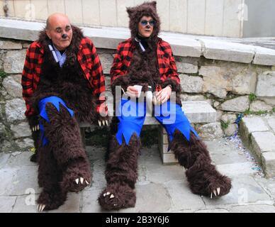 Zwei als Füchse verkleidete Männer ruhen vor dem Karnevalsumzug - Stockfoto
