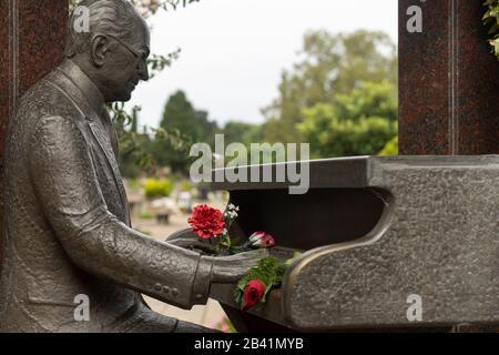 Denkmal zu Ehren des Musikers Osvaldo Pugliese in der Sektion Persönlichkeiten auf dem Chacarita-Friedhof mit frischen Rosenblüten auf der Statue - Stockfoto