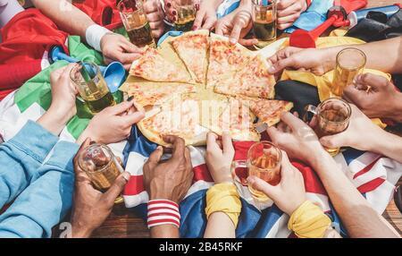 Hände Draufsicht über Fußballfans, die Pizza teilen und halbe Pint Bier trinken - Sportfans haben nach dem Spiel Spaß - Freundschaftskonzept mit soc - Stockfoto