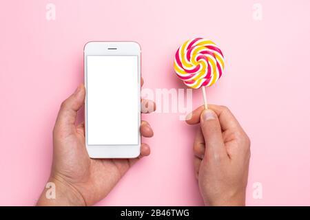 Buntes Lolipop und Handy in der Hand auf pinkfarbenem Hintergrund, Techologie und Kinderbonbons Draufsicht - Stockfoto