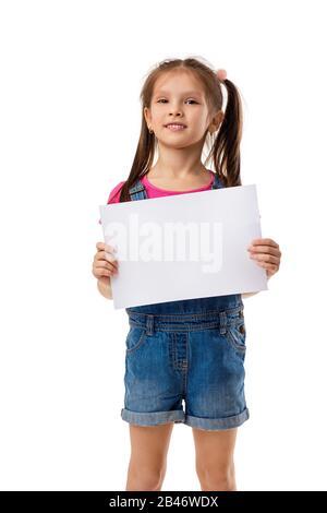 Süßes Kind mit leerem Rohling, isoliert auf weißem Hintergrund. Kind mit Plazardbrett für Ihren Text. Mädchen mit weißem Blatt Papier. Kopierbereich - Stockfoto