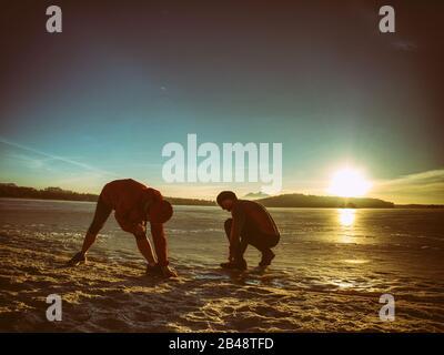 Frau und Mann, die sich vor dem Lauf in der Winternatur ausdehnen. Zwei Sportlerinnen arbeiten im Winter an einem See