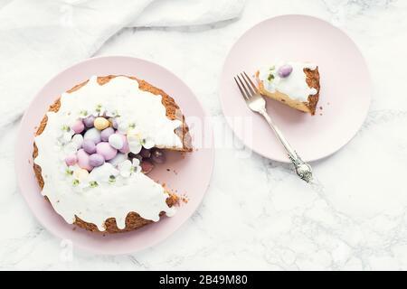 Glasierter osterkuchen mit Blumen und kleinen Schokoladeneiern, Süßigkeiten auf weißem Marmorhintergrund. Frohe Ostern. Draufsicht. Kopierbereich. - Stockfoto