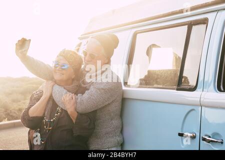 Reise- und Alternative-Leute-Urlaubskonzept für Senioren im Ruhestand Lifestyle-Paare, die selfie Bild für soziale Medien machen - Oldtimer im Hintergrund - Sunset Sunlight und Forever Konzept - Stockfoto