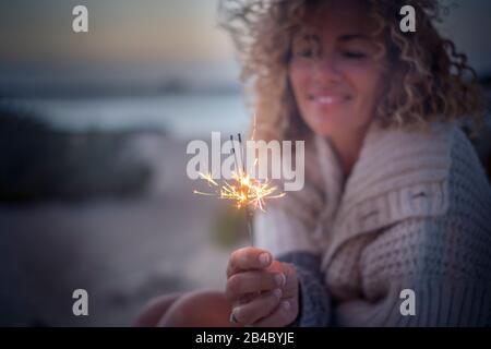 Romantische und reisefarbene Menschen junge fröhliche, lockige Frau mit Glanz im Morgengrauen des Abends im Freien - Fokus auf Hand und Feuerlicht - Freiheitskonzept - Stockfoto