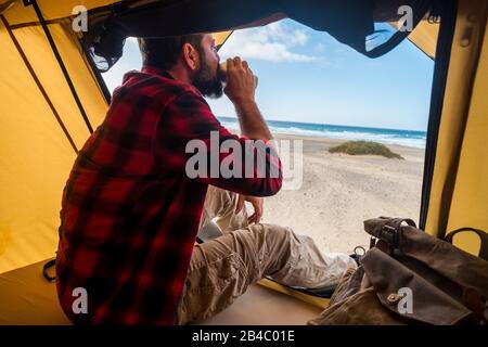 Reise- und Alternativ-Hotel-Raumbestimmungskonzept mit Menschen einsamer Mann, der in einem Zelt im freien Campen am Strand einen Kaffee trinkt, um Urlaub mit unterschiedlichem Lebensstil zu verbringen - Freiheit und Meer genießen - Stockfoto