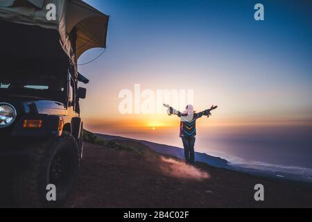 Reise- und Glückskonzept für Menschen mit Wanderlust - Frau mit farblich warmer Kleidung genießt Freiheit und Sonnenuntergang in der Nähe eines Autos mit Zelt auf dem Dach - Unabhängigkeit und wilder Reisender Lifestyle weiblich - Stockfoto