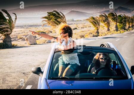 Glück und Reise-Lifestyle-Leute - Paare von Frauen Erwachsene Freunde, die mit einem blauen Cabrio-Auto fahren und reisen - aus dem Dach eine hübsch lockige blonde Frau, die die Reise schaut und genießt - Stockfoto