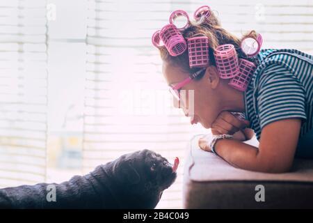 Liebe im lustigen Moment mit Frau legte sich auf das Sofa mit pinkfarbenen Lockensteinen auf den Haaren und schwarzem lieblichem Pughund, der sie küsst oder einen schönen Ausdruck macht - Freundschaft mit Tieren Konzept - Stockfoto