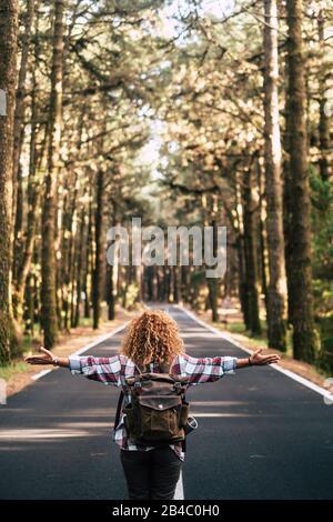 Alternatives Reisekonzept mit geschweifter Hüftfrau von hinten öffnet seine Arme und spürt die Freiheit der Natur im Freien inmitten einer Straße - Glück und Wanderlust - Stockfoto