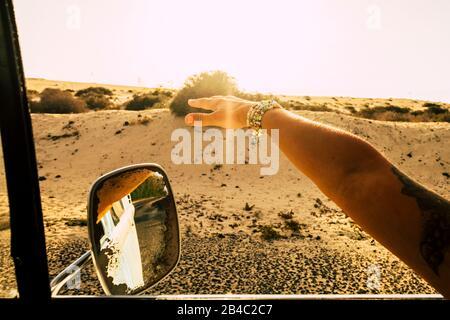Reise- und Freiheitskonzept für Menschen mit alternativem Lebensstil - Nahaufnahme einer kaukasischen Frau vor dem Fenster des Oldtimers, der auf Reisen mit dem Wind spielt - Wüste im Hintergrund und Sonnenlicht - Stockfoto