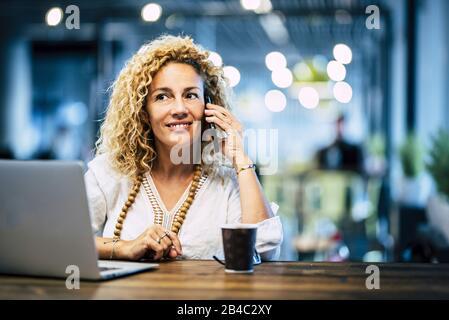 Fröhliche schöne Mitte. Jung. Frau setzt sich hin. Kaffee genießen - Telefonanrufzeit und Laptop auf. Der Tisch - Reise- und Technikkonzept für moderne Trendmenschen - Stockfoto
