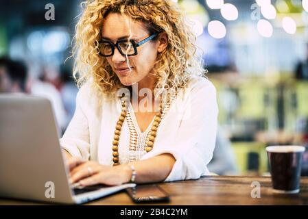 Moderne Erwachsene kaukasische Frau, die an einem Laptop an ihrem Desktop arbeitet - Leute, die mit Technologiekonzept arbeiten - Internetverbindung und entschärfter Hintergrund - Stockfoto