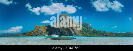 El Nido, Boot der Fischer in Blue Bay mit Panoramablick auf cadlao Insel im Hintergrund, Palawan, Philippinen. Stockfoto