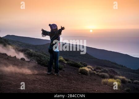 Menschen, die bei Sonnenuntergang offene Natur am Berg genießen - aktive Frau im Freien, Freizeitaktivität mit offenen Armen - Reisekonzept für Freiheit und alternativen Lebensstil - Stockfoto