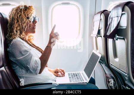 Schöne weibliche Passeger des Flugzeugs benutzen einen persönlichen Laptop an Bord mit wifi-Internetverbindung und bitten um Hostess Hilfe - Reisen für Business modern People Konzept