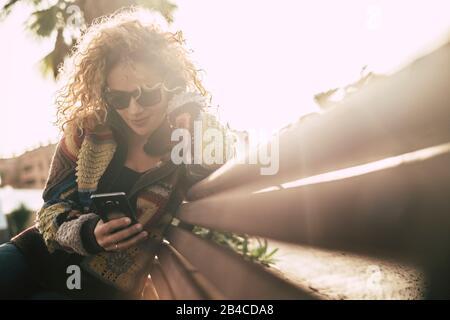 Farben in der Herbstsaison mit schöner, erwachsener, attraktiver blonder lockiger Frau verwenden ein Handy, das auf einem Beanch sitzt und bei Freizeitaktivitäten im Outoor-Bereich aktiv ist - Sonne mit Hintergrundbeleuchtung und hellem Hintergrund