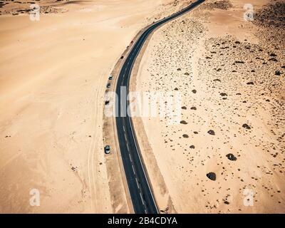 Senkrechte Draufsicht auf die schönen langen schwarzen Asphalt Durchquerung der Wüste Sand Dünen - Travel Concept und alternative arides Klima ändern, malerischen Ort - Stockfoto