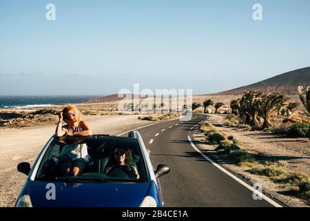 Zwei Frauen in einem blauen Auto, die gemeinsam Spaß haben zu reisen - ein Paar fröhlicher Freunde reisen in einem Cabrio-Auto an einem sonnigen Ferien-Sommertag - Meer und Natur im Hintergrund - Stockfoto