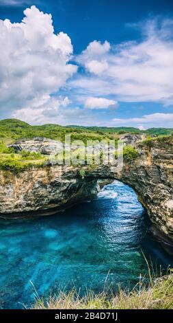 Felsenküste von Nusa Penida. Steinbogen über dem Meer. Broken Beach, Nusa Penida, Indonesien. Vertikaler Schuss - Stockfoto