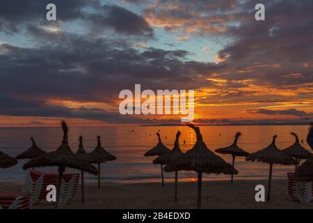 Ansicht der strohgedeckten Sonnenschutz sonnenschirme Silhouette gegen die Sonne bei s'Arenal, Palma de Mallorca, Mallorca, Balearen, Spanien - Stockfoto