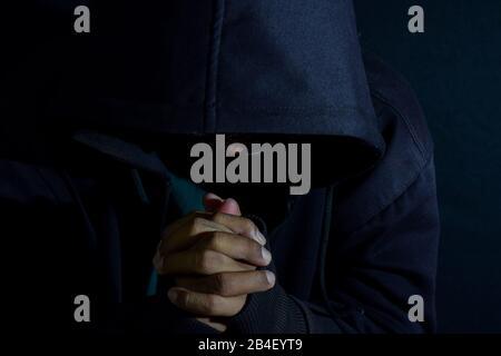 Junger Mann huldigt und betet im Grausamkeiten auf dunkelschwarzem Hintergrund. Christlicher Glaube oder gottesbegriff. Selektiver Fingerfokus