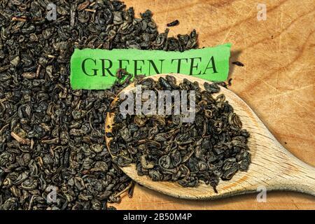 Getrocknete Blätter aus grünem Schießpulvertee auf einem Holzlöffel, mit vielen aufgerollten Blättern auf dem Hintergrund und einem Stück Papier mit Text Green Tea - Stockfoto