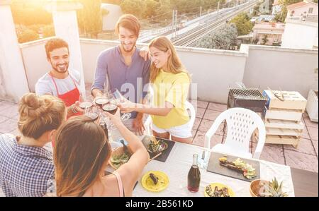 Junge Freunde jubeln mit Rotwein auf der Grillparty auf dem Dach - Fröhliche Leute machen bbq-Abendessen im Freien mit Blick auf die Stadt im Hintergrund - Konzentrieren Sie Sich auf Gläser - Stockfoto