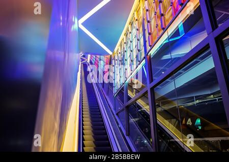 Rolltreppe mit LED-Licht neben der Technologie abstraktes, farbenfrohes Neonlicht. - Stockfoto