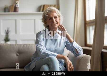 Porträt einer lächelnden Seniorin entspannen Sie sich auf der Couch - Stockfoto