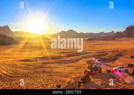 Aqaba, Jordanien - 5. Januar 2020: Menschen, die auf den roten Dünen der Wüste Wadi Rum sitzen und auf den Granitfelsen im Tal des Mondes auf Sonnenuntergang warten. So - Stockfoto