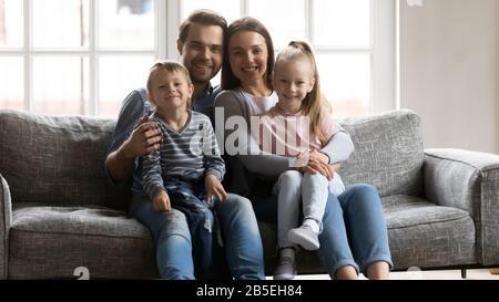 Junges Ehepaar, das auf dem Sofa ruht und die liebenswürdig jungen Geschwister hält. - Stockfoto