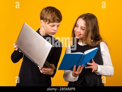 Digitale Technologie zum Lernen. Kleine Kinder nutzen neue Technologien in der Schule. Kleine Mädchen und Junge halten ES Buch und Laptop. Technologie im Bildungswesen. Bildungstechnologie. E-Learning. Online-Kurse. - Stockfoto