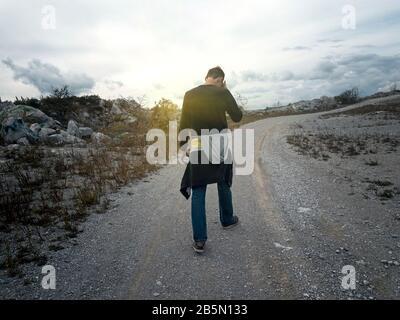 Der Mensch geht bei Sonnenuntergang auf der Bergstraße entlang Stockfoto
