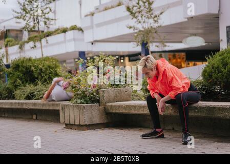 Junge weibliche Läuferinnen, die während einer Trainingsroutine in der Stadt eine Pause einlegen - Stockfoto
