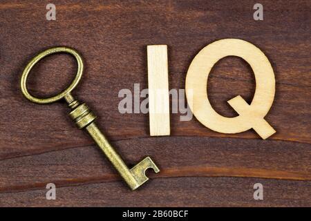 Intelligenzquotient, iq-Test, Hirnkonzept, Schlüssel mit Buchstaben auf braunem Holzhintergrund - Stockfoto