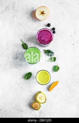 Bunte Smoothie-Getränke für ein gesundes Detox-Frühstück, Draufsicht, Kopierraum. Drei verschiedene grüne, gelbe, violette Smoothies mit Zutaten. Veganer Rohstoff - Stockfoto