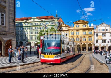 Moderne Straßenbahn auf Kopfsteinpflaster zwischen bunten Häusern in Der Prager Altstadt, Tschechien. - Stockfoto