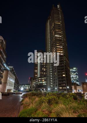 London, England, Großbritannien - 3. März 2020: Shakespeare Tower und andere Apartmentgebäude werden nachts im brutalistischen Barbican Estat der City of London angezündet - Stockfoto