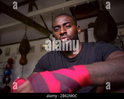 Porträt Des Männlichen Boxertrainings In Der Sporthalle Umschließt Die Hände Stehend Neben Der Stanztasche - Stockfoto