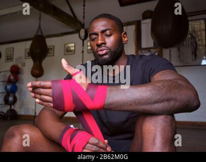 Boxertraining Für Männer In Der Sporthalle Umschließt Die Hände Stehend Neben Der Stanztasche - Stockfoto